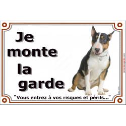 Bull Terrier Tricolore assis, plaque portail je monte la garde, risques périls, pancarte affiche panneau attention au chien